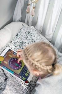 Barn ligger i sängen och spelar Zcooly på iPad